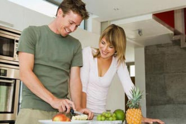 A couple preparing fruit in the kitchen