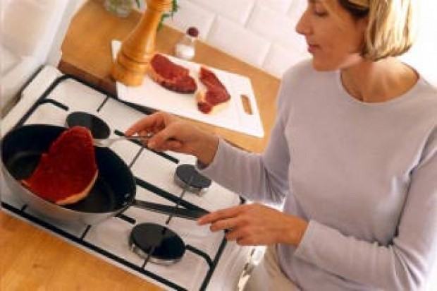 A woman frying steak in her kitchen