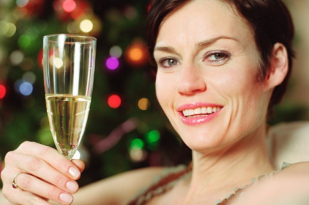 A woman drinking a glass of champagne by the Christmas tree