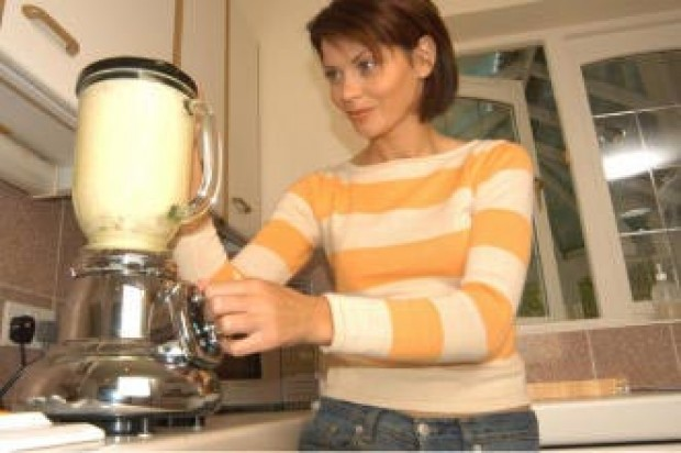 A woman in her kitchen belnding smoothies