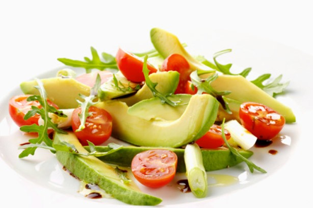A plate of avocado and cherry tomato salad