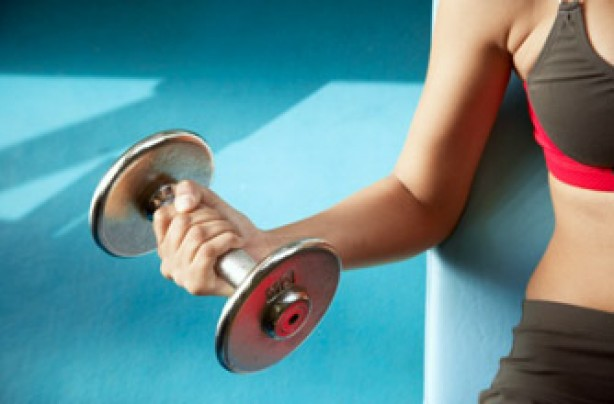 A woman exercising by lifting weights