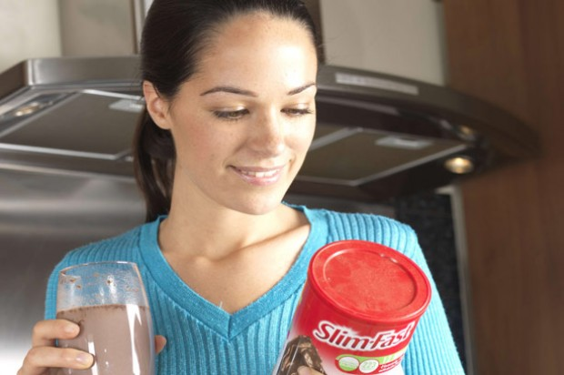A woman drinking a chocolate Slim.Fast milkshake in her kitchen