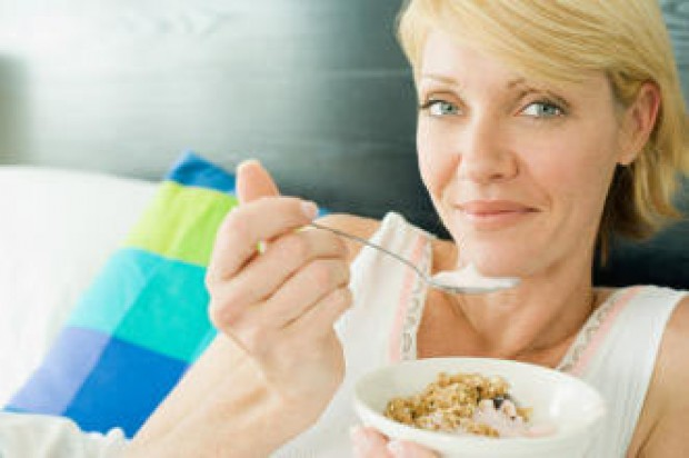 A woman eating a breakfast of cereal and yogurt