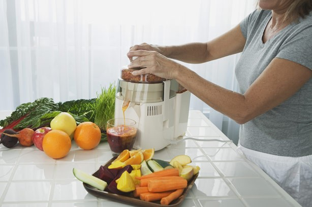 A woman in the kitchen preparing vegetable and fruit juice smoothie