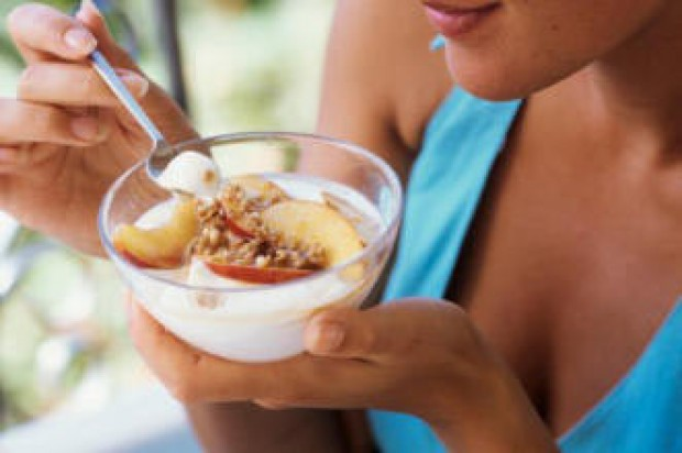 A woman eating yogurt and fruit