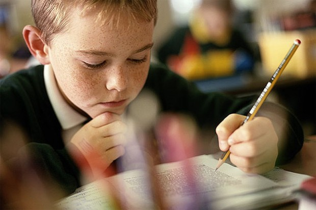 Boy in classroom with pencil and workbook