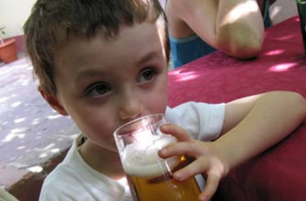 A Child drinking a glass of beer