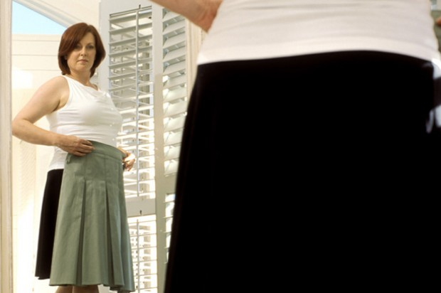 A woman trying on clothes in front of a mirror