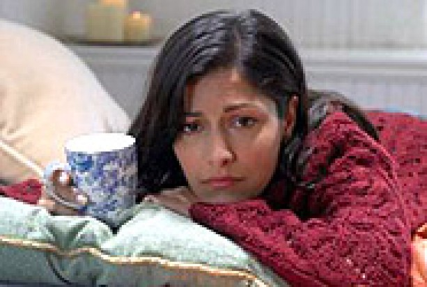 Woman lying on a bed depressed