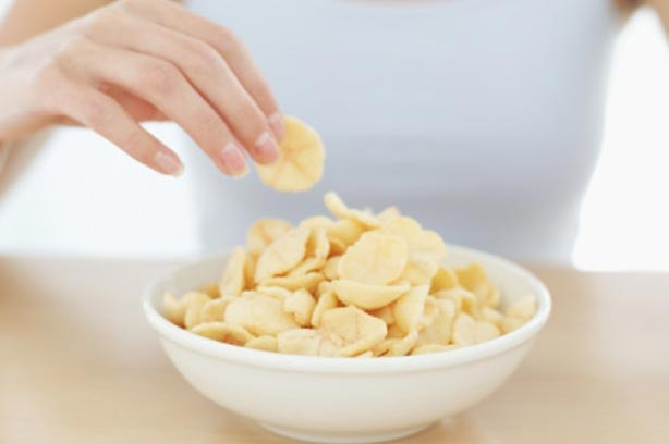 A woman eating a bowl of crisps