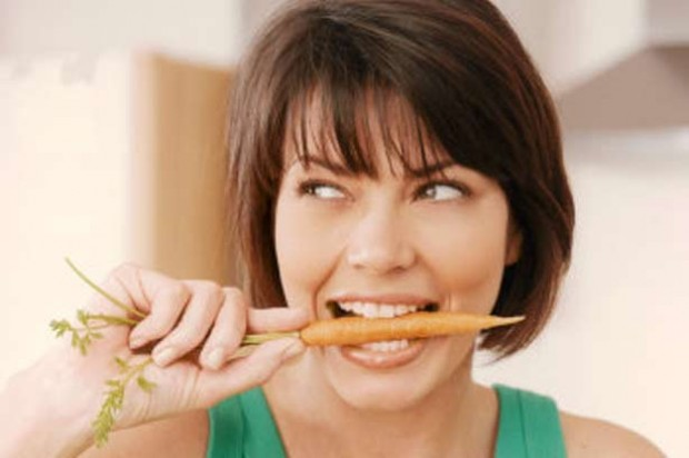 A woman eating a raw carrot