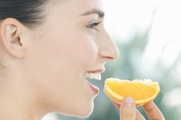 A woman snacking on an orange