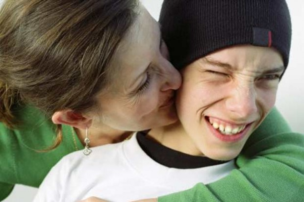 Love teenagers kiss hug mother son