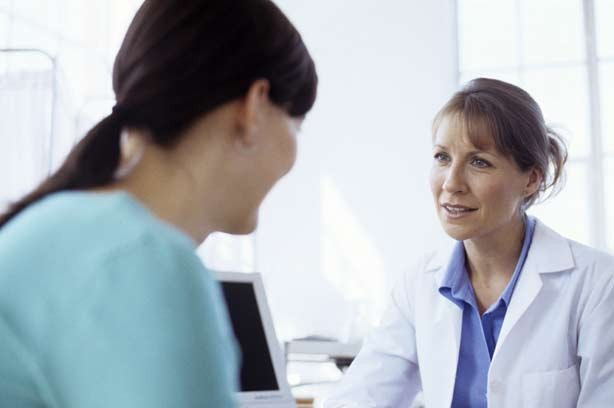 A woman talking to a female doctor
