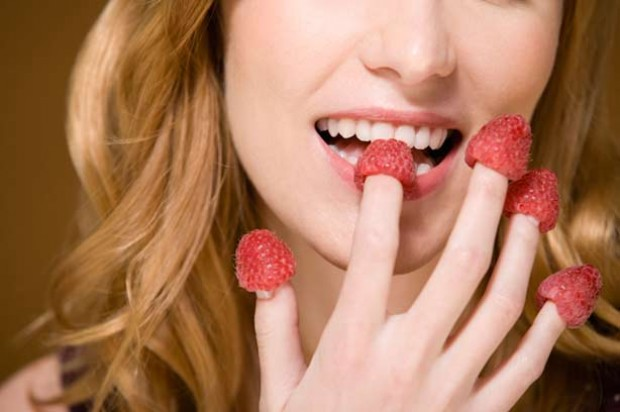 A woman eating raspberries