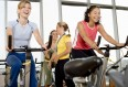 Women on exercise bikes taking part in a spin class