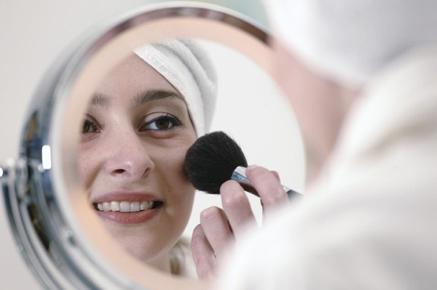 woman putting on makeup in mirror photo