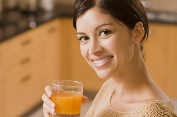 A woman drinking a glass of juice