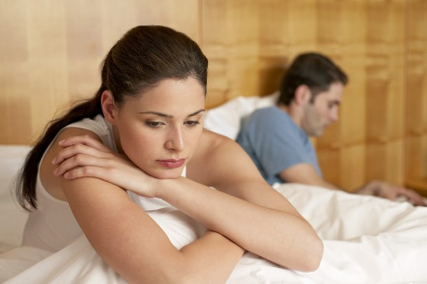 Woman sat on a bed looking sad with a man sat behind her