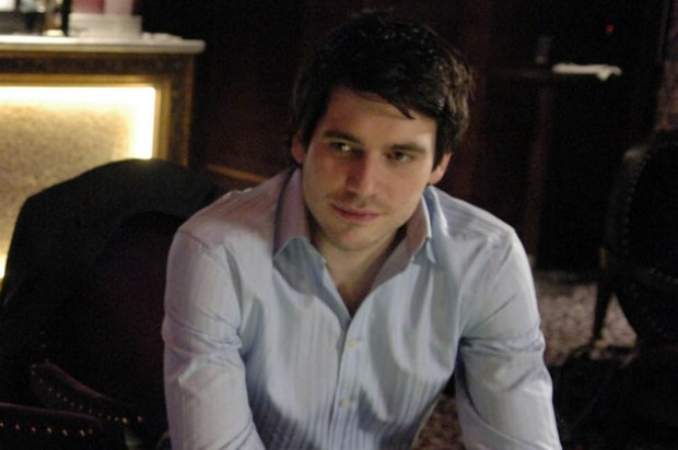 Rob James-Collier who plays Liam Connor in Coronation Street sits on a chair looking thoughtful_ITV images