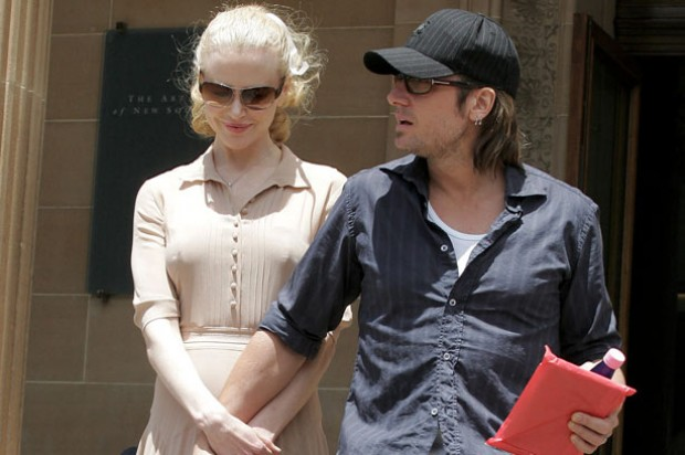 Pregnant Nicole Kidman and husband Keith Urban walk down steps with his hand covering her baby bump