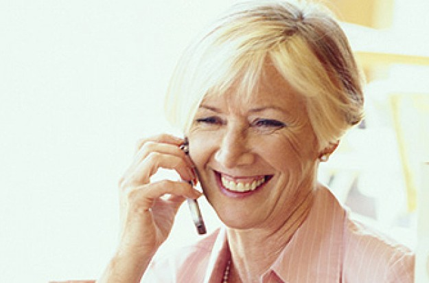 A woman smiling and talking while on a mobile phone