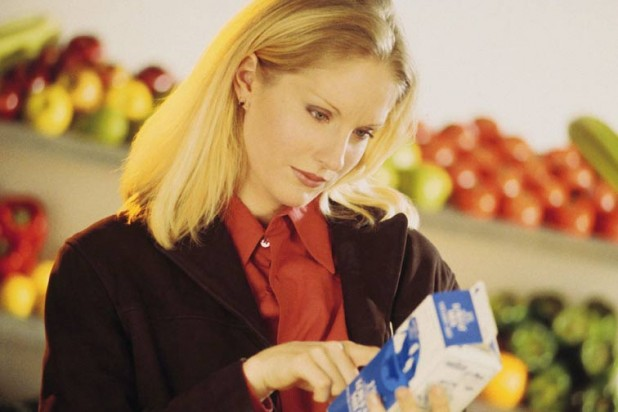 Woman looking at food label in supermarket