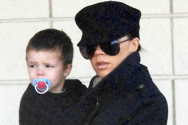 Victoria Beckham carries her youngest son Cruz with a dummy in his mouth_rex