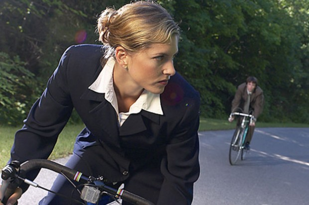 woman cycling with a man behind her on a bicycle