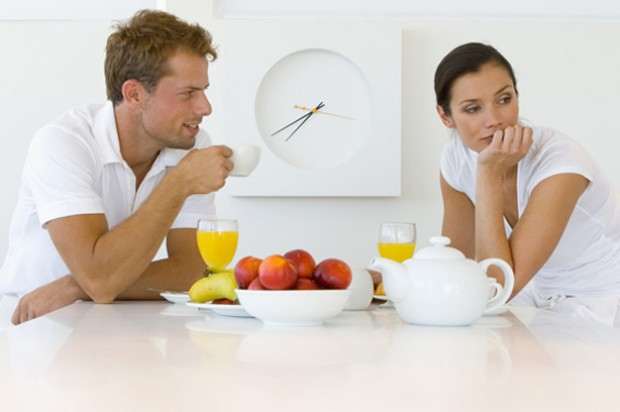 Man and woman sat eating breakfast the woman looks bored