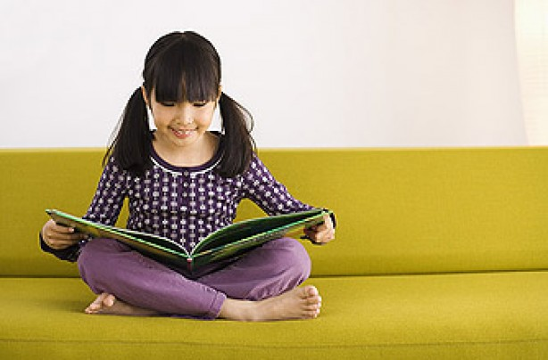 A young girl reading a book on a sofa