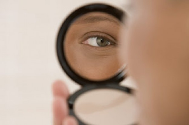 Woman looking in mirror of compact