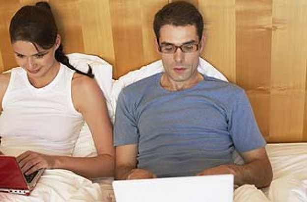 A couple in bed not talking, using laptops