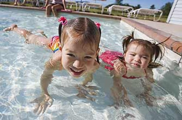 Two kids playing in a swimming pool