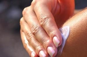 Woman applying cream to shoulder