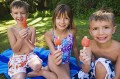 Three children enjoying ice lollies in the shade