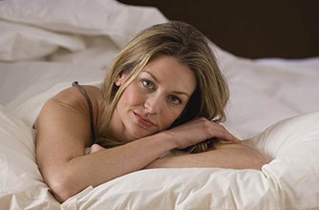 Woman unhappy lying on a bed