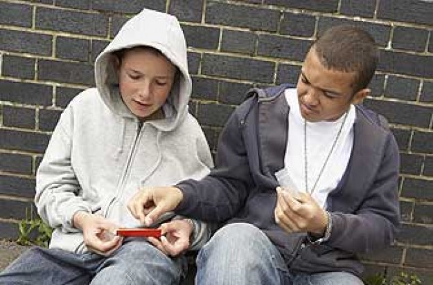 Two teenage boys rolling a joint_ jupiter unlimited