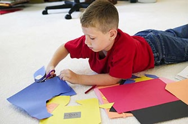 A boy using paper and scissors to make a scrapbook