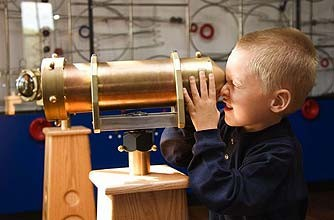 Boy in a museum looking through a telescope