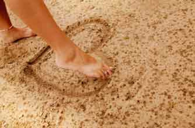 Woman making heart shape with her foot in the sand_rex