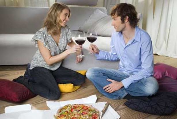 Couple eating pizza and drinking wine