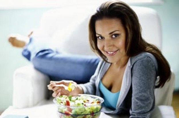 Woman eating salad and wearing jeans__Photolibrary