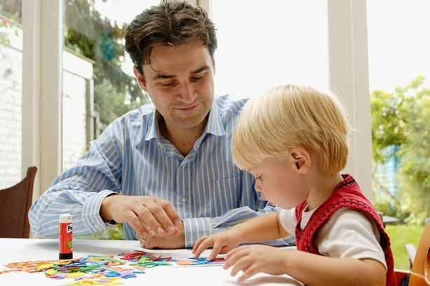 A dad helping his child with drawing and craft