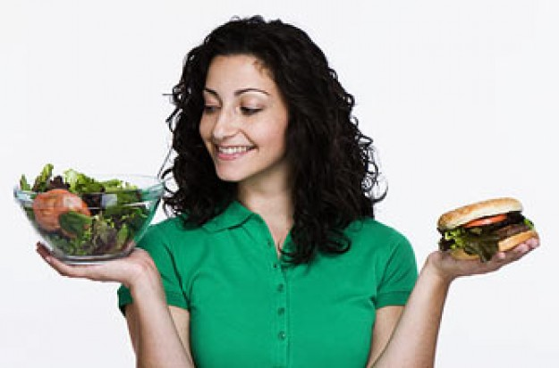 Woman choosing between salad and burger_Photolibrary