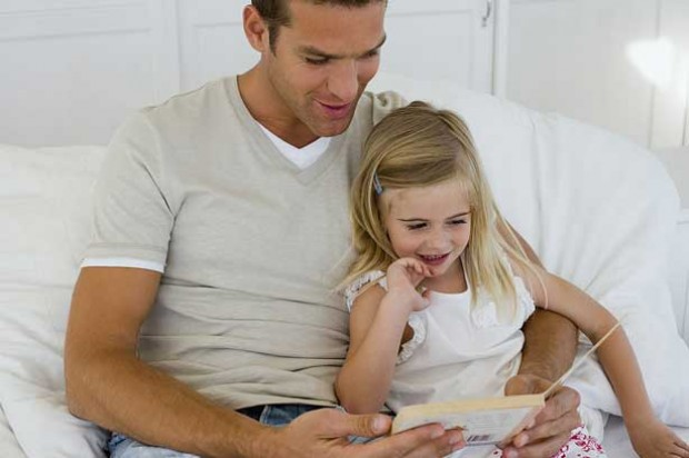 A dad and his daughter reading together