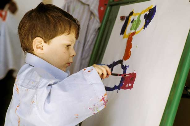 A boy painting at school