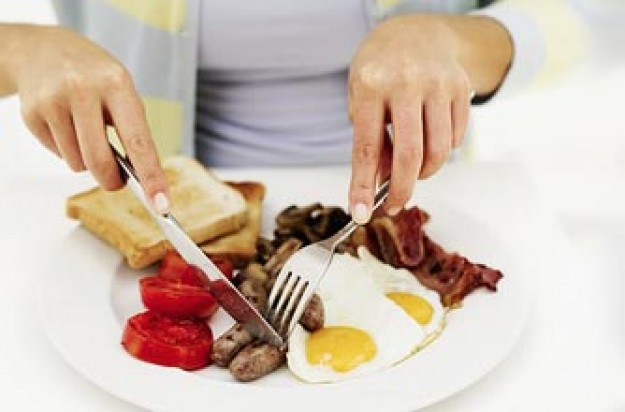 Woman eating eggs and bacon_Photolibrary