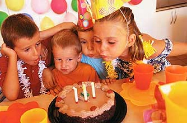Kids blowing out candles on a birthday cake